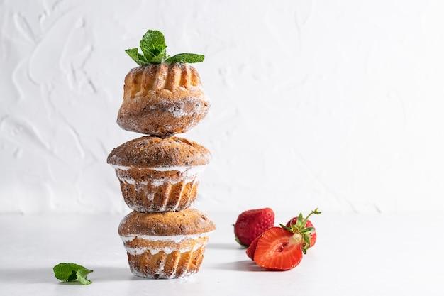 Frische hausgemachte cupcakes mit minzblättern und erdbeeren auf weißem hintergrund.