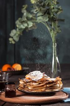 Frische hausgemachte französische crepes mit eiern, milch und mehl, gefüllt mit marmelade auf einem vintage-teller