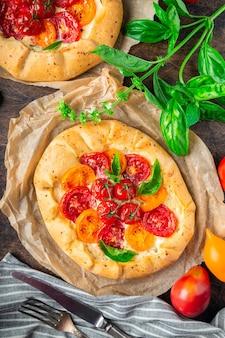 Frische hausgemachte galettes mit tomaten-ricotta-käse und basilikum auf rustikalem sperrholz-hintergrund