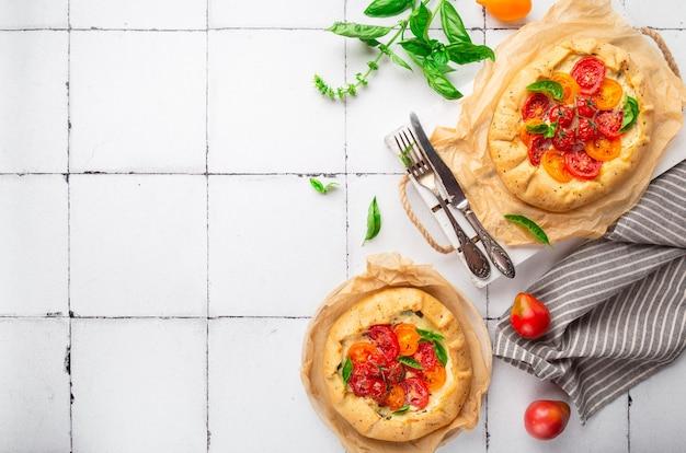 Frische hausgemachte galettes mit tomaten-ricotta-käse und basilikum