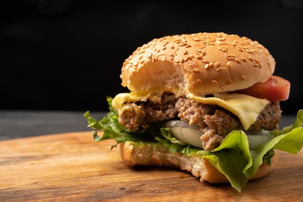 Frische hausgemachte hamburger, leckeres frisches gemüse, das auf ein schneidebrett gebissen wird