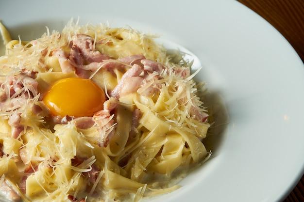 Frische hausgemachte italienische carbonara-nudeln mit rohem eigelb, parmesan, weißer soße, speck in der weißen schüssel auf hölzernem hintergrund.