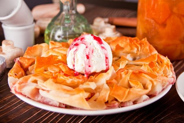 Frische hausgemachte kirsch-filo-teig-torte mit vanilleeis