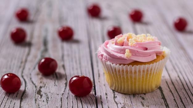 Frische hausgemachte kirschbeeren-cupcakes auf holztisch