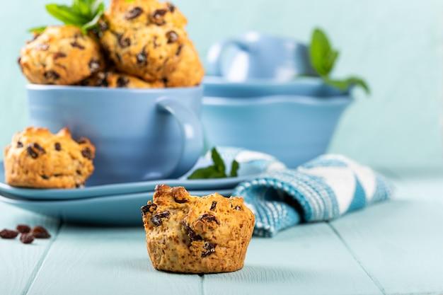 Frische hausgemachte leckere rosinenmuffins in blauer tasse, zuckerfrei. gesundes lebensmittelkonzept mit kopierraum