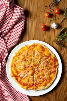Frische hausgemachte margarita-pizza auf einem hölzernen hintergrund in der zusammensetzung mit einem roten tuch und olivenöl. italienische küche. draufsicht food foto