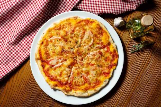 Frische hausgemachte margarita-pizza auf einem hölzernen hintergrund in der zusammensetzung mit einem roten tuch und olivenöl.