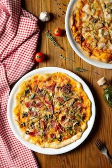 Frische hausgemachte pizza mit schinken, kapern, oliven auf einem hölzernen hintergrund in der zusammensetzung mit einem roten tuch und olivenöl.
