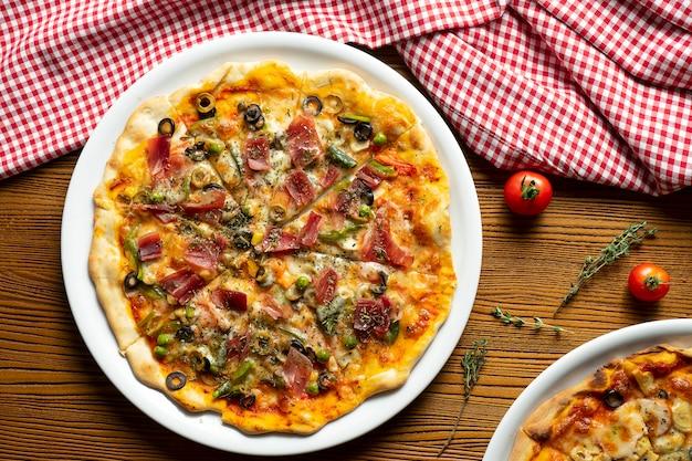 Frische hausgemachte pizza mit schinken, kapern, oliven auf einem hölzernen hintergrund