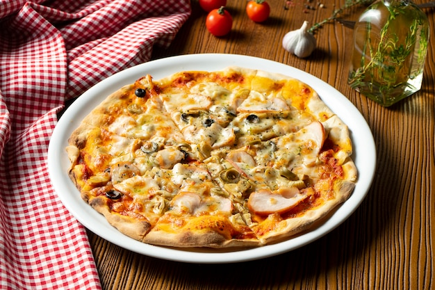 Frische hausgemachte pizza mit schinken, pilzen und oliven auf einem hölzernen hintergrund