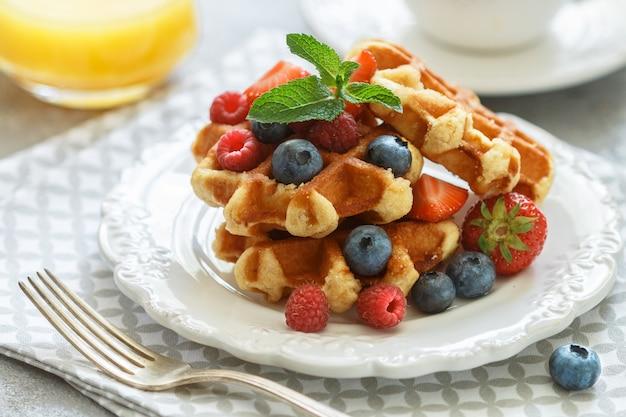 Frische hausgemachte waffeln mit himbeeren, erdbeeren, heidelbeeren und honig