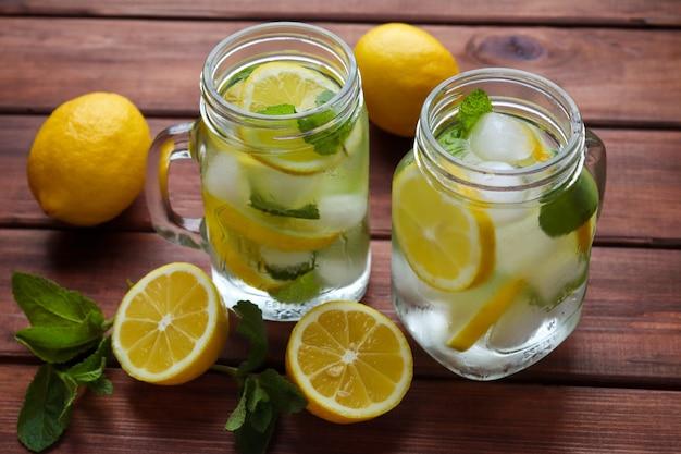 Frische hausgemachte zitruslimonade mit zitronenminze und eis auf einem holztisch sommer erfrischende getränke