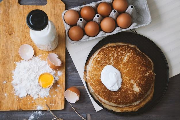 Frische, heiße pfannkuchen in einer pfanne, eier, milch, mehl auf einem holztisch. ansicht von oben