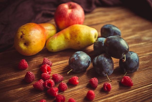 Frische herbstfrüchte liegen auf einem holztisch. ernte von frischem obst auf dem tisch. frische äpfel, birnen, pflaumen, himbeeren, melone auf dem tisch.