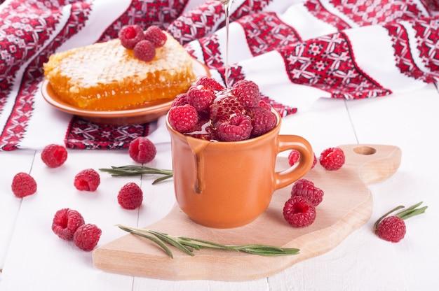 Frische himbeeren in einer schüssel mit honig und rosmarin auf einem hölzernen hintergrund