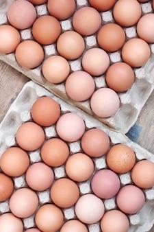 Frische hühnerbraune eier beim verpacken auf einem bauholzfußboden