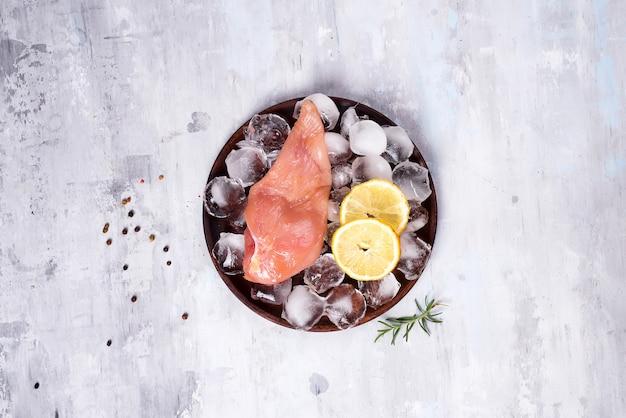 Frische hühnerbrust des rohen fleisches auf einer hölzernen platte mit zitronenscheibe und -eis. schlanke proteine.