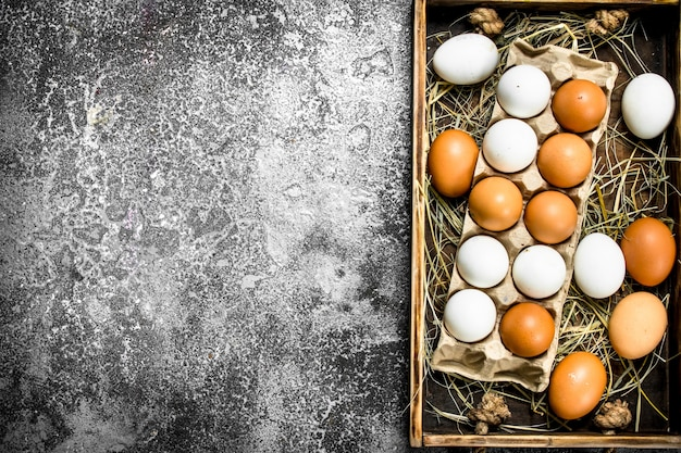 Frische hühnereier auf einem alten tablett. auf einem rustikalen hintergrund.