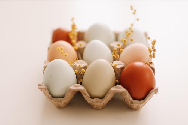Frische hühnereier in natürlichen farben und schattierungen in einer recycelten schachtel