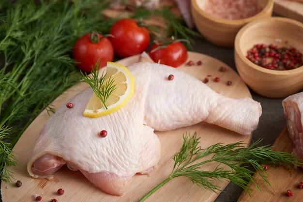Frische hühnerfleischportionen zum kochen und grillen mit frischem gewürz. rohes ungekochtes hähnchenschenkel auf schneidebrett.