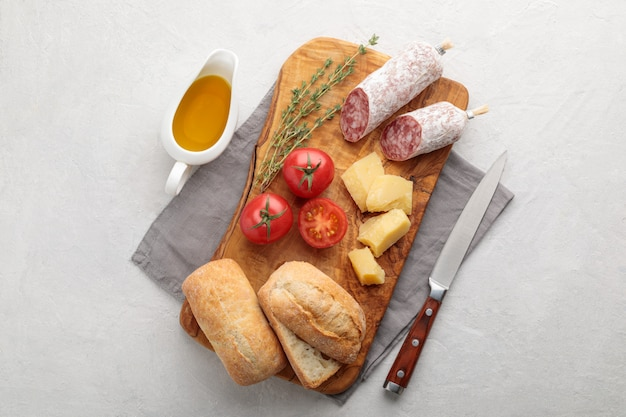 Frische italienische lebensmittelzutat zum frühstück sandvich brot, tomate, olivenöl, thymian, parmesan und salami auf weißem hintergrund. bildkopierplatz und draufsicht