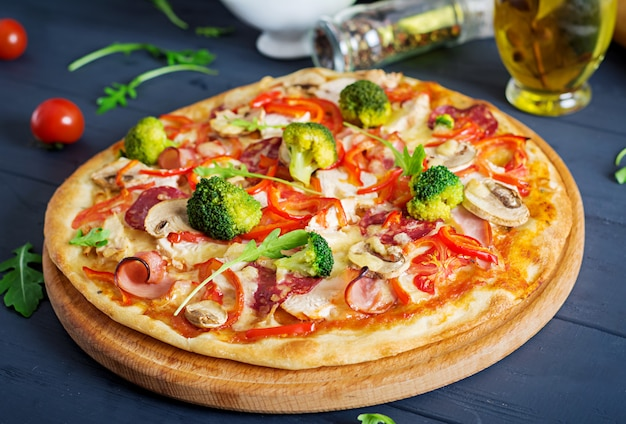 Frische italienische pizza mit hühnerleiste, pilzen, schinken, salami, tomaten, brokkoli, käse an auf schwarzem hintergrund.
