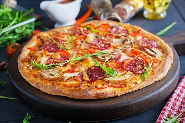 Frische italienische pizza mit hühnerleiste, pilzen, schinken, salami, tomaten, käse auf einem schwarzen hintergrund.