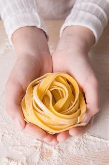 Frische italienische rohe selbst gemachte teigwarenbandnudeln in den händen einer jungen frau. italienische pasta