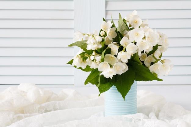 Frische jasminblüten in einer vase auf holz