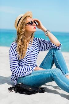 Frische junge frau in der kühlen sonnenbrille und im strohhut, die auf dem sonnigen tropischen strand sitzen