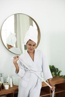 Frische junge frau mit handtüchern nach dem bad gewickelt, die kamera lächelnd. hautpflegekonzept, morgenroutine.