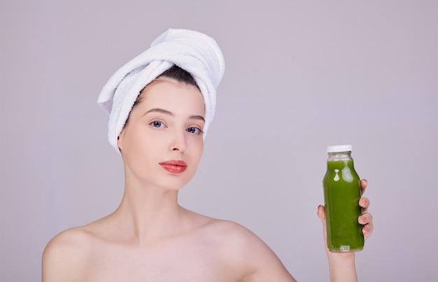 Frische junge halbnackte frau hält in ihrer linken hand einen grünen smoothie in einer flasche.