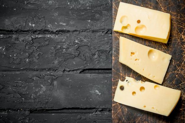 Frische käsestücke auf dem brett. auf schwarzem rustikalem hintergrund.