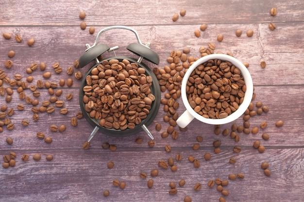 Frische kaffeebohnen in einer tasse und wecker auf dem tisch