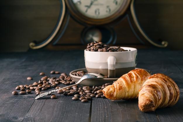 Frische kaffeebohnen und croissants auf holzoberfläche