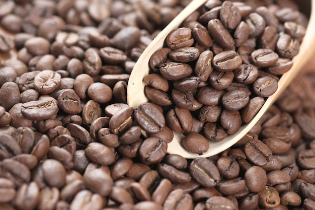 Frische kaffeebohnen und löffel auf dem tisch.