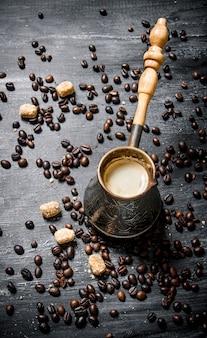 Frische kaffeekanne mit rohrzucker und gerösteten körnern. auf einer schwarzen tafel.
