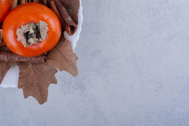 Frische kaki-früchte mit getrockneten blättern in weißer schüssel.