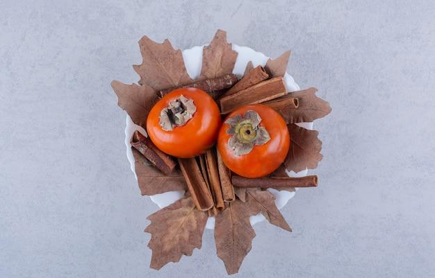 Frische kakifrüchte mit getrockneten blättern in weißer schüssel.