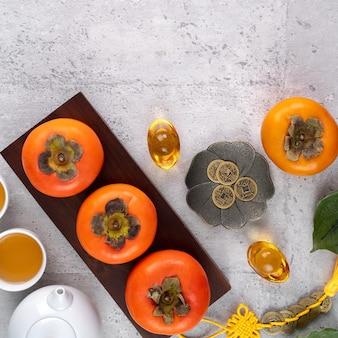 Frische kakis auf grauem tischhintergrund für chinesisches neujahrsfruchtdesign, wörter auf der goldenen münze bedeuten den dynastienamen, den es machte.
