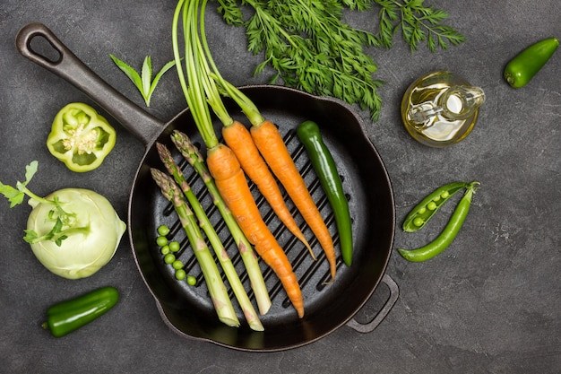 Frische karotten mit grünen spitzen, grüne paprikaschote und spargel in der pfanne. flasche olivenöl, kohlrabi, paprika und grüne erbsen auf dem tisch. schwarzer hintergrund. flach legen