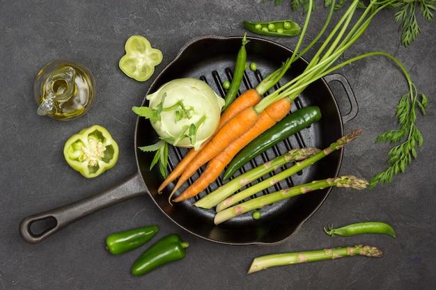 Frische karotten mit grünen spitzen, grüne paprikaschote und spargel in der pfanne. flasche olivenöl, paprika und grüne erbsen auf dem tisch. schwarzer hintergrund. flach legen