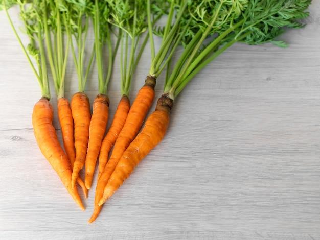 Frische karotten nur aus dem garten. orange karotten mit einem grünen stiel auf einem hellen hintergrund. appetitliches gesundes gemüse.