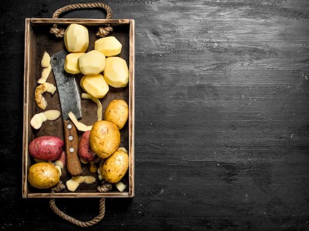 Frische kartoffeln auf einem tablett. auf der schwarzen tafel.