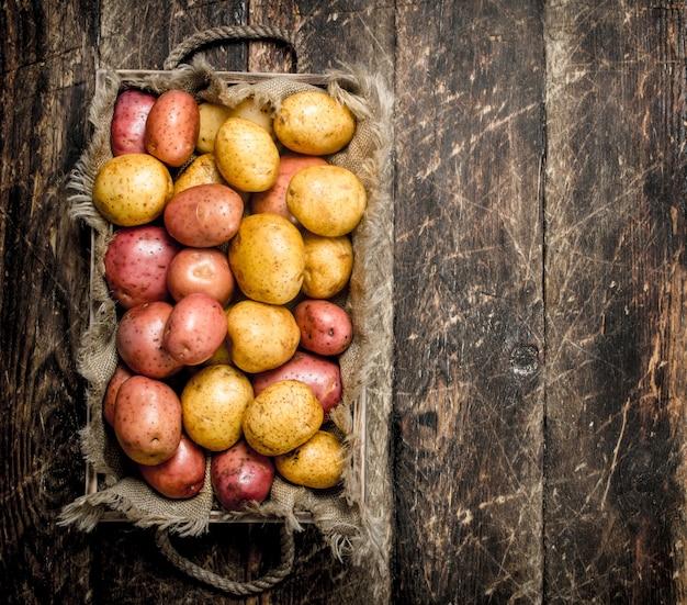 Frische kartoffeln auf holztablett auf holztisch.