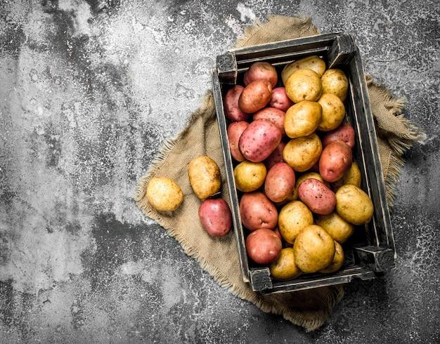 Frische kartoffeln in einer box. auf einem rustikalen hintergrund.