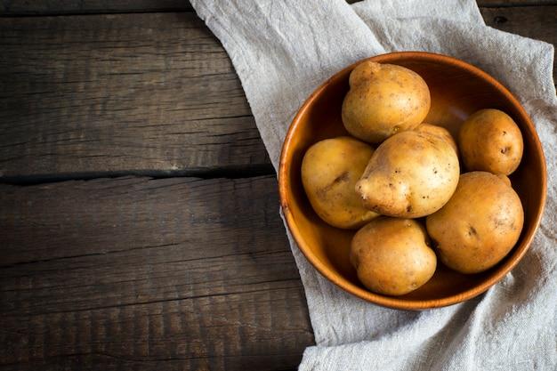 Frische kartoffeln in einer schüssel auf dem alten holztisch.