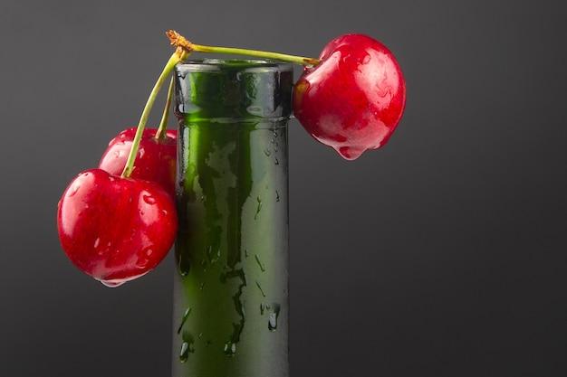 Frische kirschbeere mit auf einer grünen flasche. gesundes essen zum frühstück. früchte der vegetation. fruchtdessert