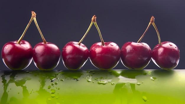 Frische kirschbeere mit wassertropfen auf einer grünen flasche. gesundes essen zum frühstück. früchte der vegetation. fruchtdessert