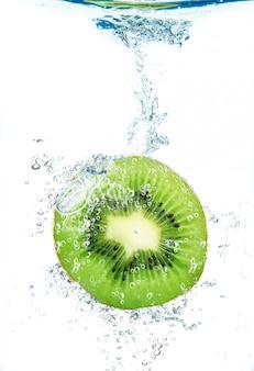 Frische kiwi, die in wasser fällt